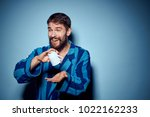 Small photo of adjective man in a bathrobe with a blank mug on a blue background