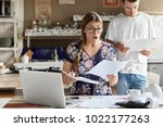 Small photo of Young female looks with shocked expression into papers, recieve high taxes and had to pay much money for bills, sits against kitchen interior, her husband stands behinds, studies documents attentively