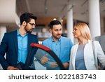 young couple choosing new car... | Shutterstock . vector #1022183743