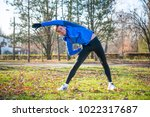 young male runner stretching in ... | Shutterstock . vector #1022317687