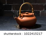 brown ceramic teapot on a dark... | Shutterstock . vector #1022415217