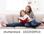 happy girl and her mom reading... | Shutterstock . vector #1022520913