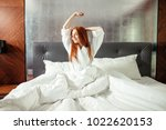 redhead woman stretching in bed ... | Shutterstock . vector #1022620153