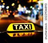 Small photo of Taxi sign on the roof of a taxi at night close-up