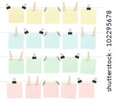 Four rows of colored blank sticky notes held on strings by various clips isolated on white. - stock photo