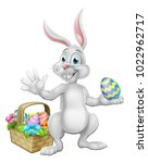 Stock vector easter bunny cartoon character rabbit holding a chocolate easter egg with a basket or hamper 1022962717