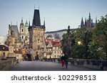 View of the Lesser Bridge Tower of Charles Bridge in Prague (Karluv Most) the Czech Republic. Couple walking in the morning. - stock photo