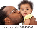 A father holding kissing his beautiful six month old baby girl on the cheek. Isolated on a white background. - stock photo