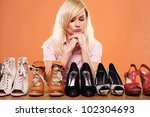 Fashion conscious woman looking at a row of different shoes trying to choose accessories for her outfit - stock photo
