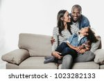 Small photo of Enjoyed parents and child sitting together with comfort. Mom and kid are looking at father standing abaft them. Copy space in left side. Isolated on background