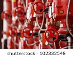 Red steam valves and other pressure equipment in industrial facility - stock photo