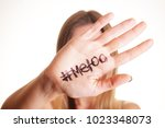 Small photo of Close up portrait of unknown young woman covering her face w/ #Metoo hashtag word on palm of hand isolated on white. Me too movement. Anti sexism protest against inappropriate behavior towards women.