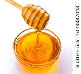 honey stick and bowl of pouring ... | Shutterstock . vector #1023387043