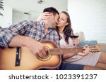 man playing guitar in living... | Shutterstock . vector #1023391237