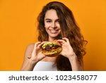 woman eat burger sandwich with... | Shutterstock . vector #1023458077