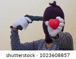 gunman holding red heart shape... | Shutterstock . vector #1023608857