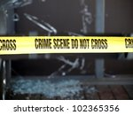 Yellow tape blocks off a crime scene with broken glass - stock photo
