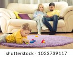 parents sit on the couch.... | Shutterstock . vector #1023739117