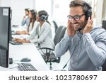 Small photo of Smiling customer service executive with headset working in call center.