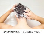 young manis washing his hair ... | Shutterstock . vector #1023877423