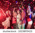 Small photo of In selective focus of Cheerful young people showered with throwing confetti on a club party.Festival Event Party with People concept.Clubber drinking.