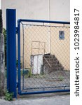 Small photo of Blue galvanized gate with forbidden sign and stone staircase inside