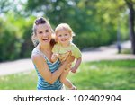 Smiling mother and baby playing in park - stock photo