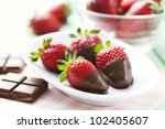 fresh strawberries dipped in dark chocolate - stock photo