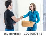 Small photo of Delivery man and woman receiver are shaking hand when receive the package box