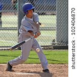A youth baseball player swings at a ball over the plate. - stock photo