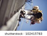 Climber ascending 300' cell tower - stock photo