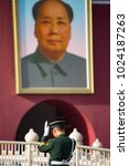 Small photo of Beijing China - April 4, 2016: Picture of guard in green with white gloves and hat at Forbidden city with chairman mao in the background