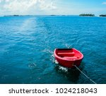 Red Dinghy Behind Sailboat