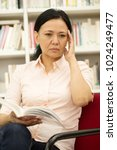 Small photo of Vertical portrait of a beautiful Asian mature woman relaxing sitting comfortably reading a book bookstore library education intelligence imagination studying learning teacher profession occupation job