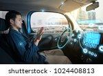 relaxed man in autonomous car.... | Shutterstock . vector #1024408813