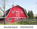 A Bright Red Barn Stands In Th...