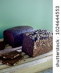 Small photo of Dark bread by green wall