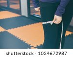woman is measuring her thigh... | Shutterstock . vector #1024672987