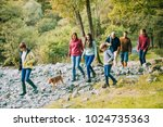 Stock photo three generation family are hiking together through the lake district with their pet dog 1024735363