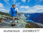 Small photo of Best Norway hike. Cute boy with hiking equipment in the mountains
