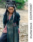 Small photo of PHONGSALY PROVINCE, LAOS - AUGUST 21, 2017: Woman from the Akha tribe with traditional headgear posing outside house in mountains of North Laos.