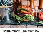 cheeseburger on a pretzel bun... | Shutterstock . vector #1025004157