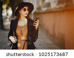 styligh woman uses her cell...   Shutterstock . vector #1025173687