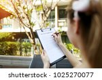 Small photo of girl travel and rent short term condo in europe. concept of traveler looking for place to live sunny day, focus on doc. close up portrait of woman hands signing rental agreement on background of