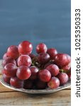 bunch of red grapes on plate on ...   Shutterstock . vector #1025350333