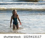 little girl playing in the waves | Shutterstock . vector #1025413117