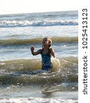 little girl playing in the waves | Shutterstock . vector #1025413123
