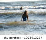 little girl playing in the waves | Shutterstock . vector #1025413237
