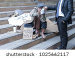 Small photo of a man is homeless or beggar wear old cloth sitting on stairs beside street or walkway with a cup for request money or coin from someone kindness and text please help on paper board