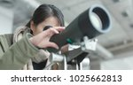 Small photo of Woman looking through telescope to observe the bird